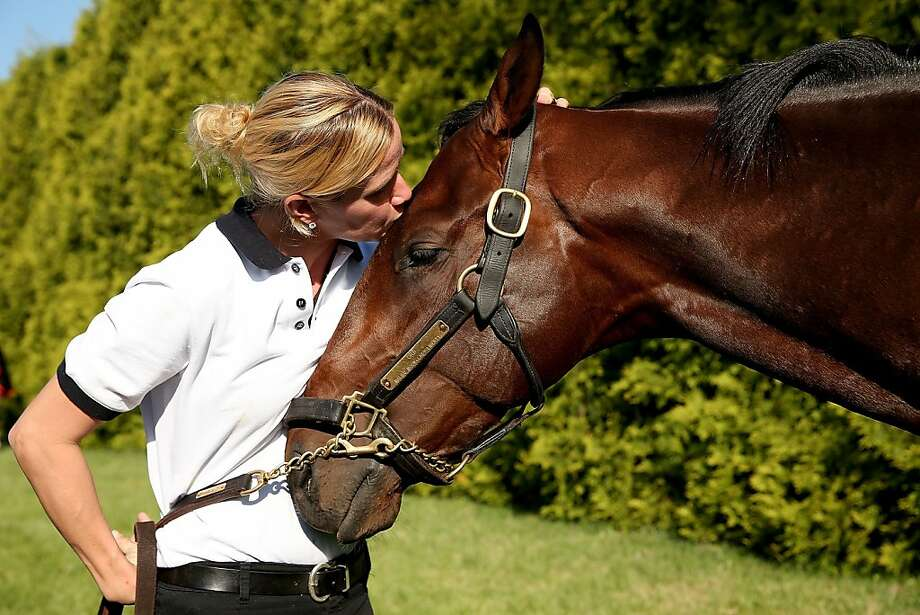 Jennifer Patterson kisses Kentucky Derby winner Orb after the morning workout in preparation for the 138th Preakness Stakes at Pimlico Race Course on May 17, 2013 in Baltimore, Maryland. Photo: Matthew Stockman, Getty Images