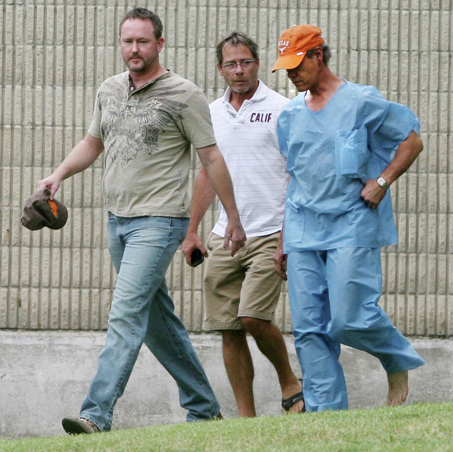 FILE - In this Aug. 8, 2012 file photo, Randy Travis, far right exits the Grayson County jail with two unknown persons, in Sherman, Texas, after being arraigned on charges of driving while intoxicated and retaliation. Travis has filed a lawsuit to prevent two state agencies from releasing a patrol car video of his 2012 DWI arrest in North Texas. (AP Photo/The Herald Democrat, Chris Jennings, File) TV OUT; MAGS OUT; TV AND MAGAZINE CALL FOR RATES TERMS; MANDATORY CREDIT Photo: Chris Jennings