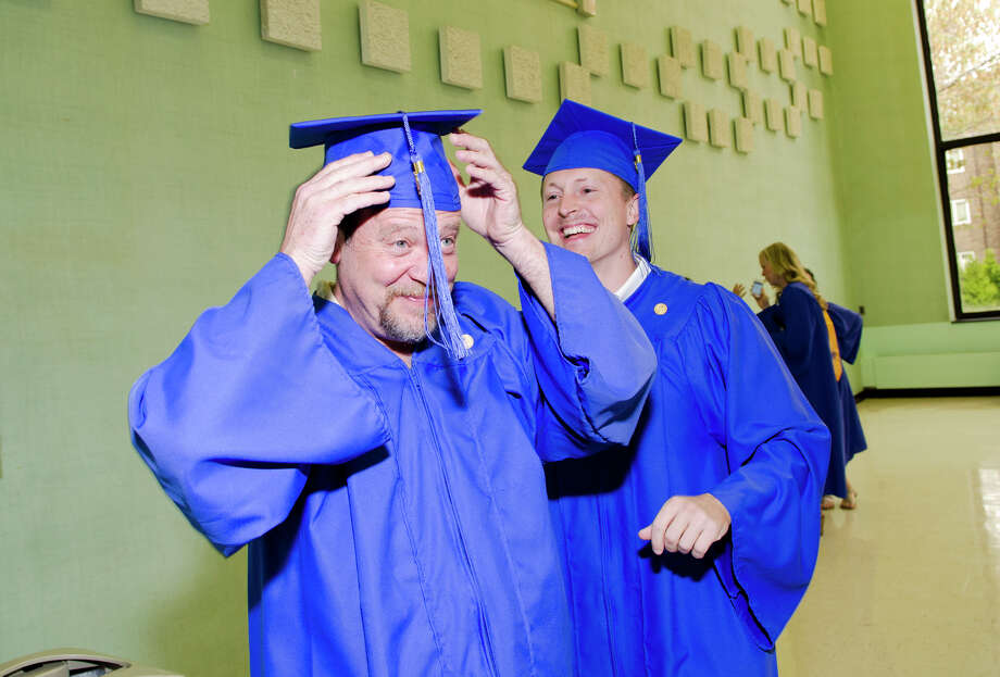 Eric Robinson, of Bridgeport, adjusts his cap with the help of Vincent Harrick, of Woodbridge, at right, in the staging area during the twenty-first annual commencement ceremony of St. Vincent's College at the Arnold Bernhard Center at the University of Bridgeport campus on Friday, May 17, 2013. Photo: Amy Mortensen / Connecticut Post Freelance