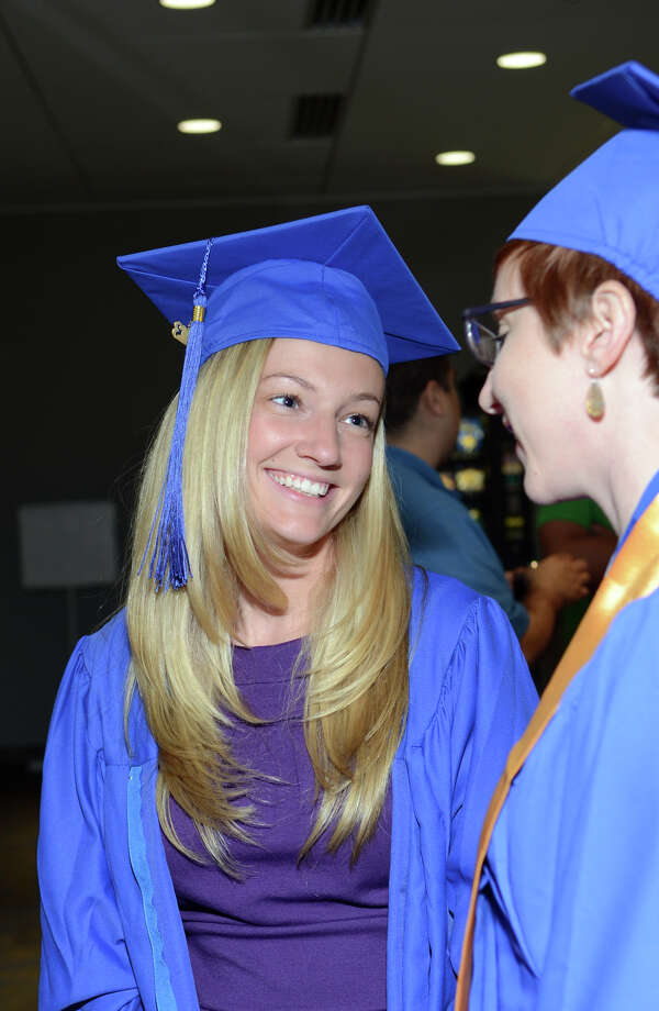 Sarah Baumbach, at left, of Watertown, shares a moment with fellow graduate, Betsy Smith, of Fairfield, during the twenty-first annual commencement ceremony of St. Vincent's College at the Arnold Bernhard Center at the University of Bridgeport campus on Friday, May 17, 2013. Photo: Amy Mortensen / Connecticut Post Freelance