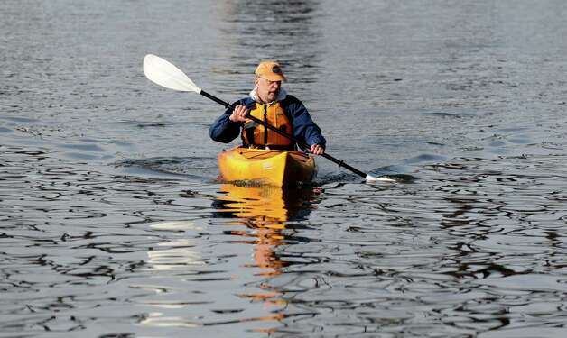 Brian Kempf of the State Parks Marine Services Bureau paddled his kayak to work Friday morning, May 17, 2013. Kempf and co-worker Ro Woodard were met by DEC Commissioner Joe Martens and others at the Corning Preserve boat launch in Albany, N.Y. Martens rode his bike to work during Green Your Commute Day. DEC partnered with State Parks, NYSERDA, EFC, and alternative transportation service providers for the first Green Your Commute Day. (Will Waldron/Times Union) Photo: Will Waldron
