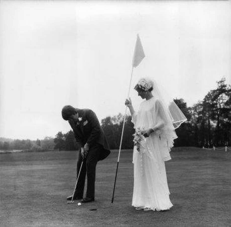 Golfer Jack Davies works on his short game on his wedding day in 1974, with his new wife as caddy, as is tradition at Sunningdale Golf Club. Photo: J. Wilds, Getty Images