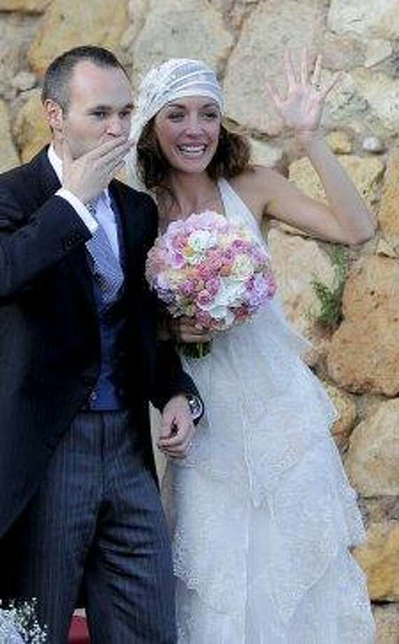 Barcelona midfielder Andres Iniesta and Anna Ortiz wave after their wedding ceremony in Altafulla, near Tarragona on July 8, 2012. Photo: JOSEP LAGO, AFP/Getty Images