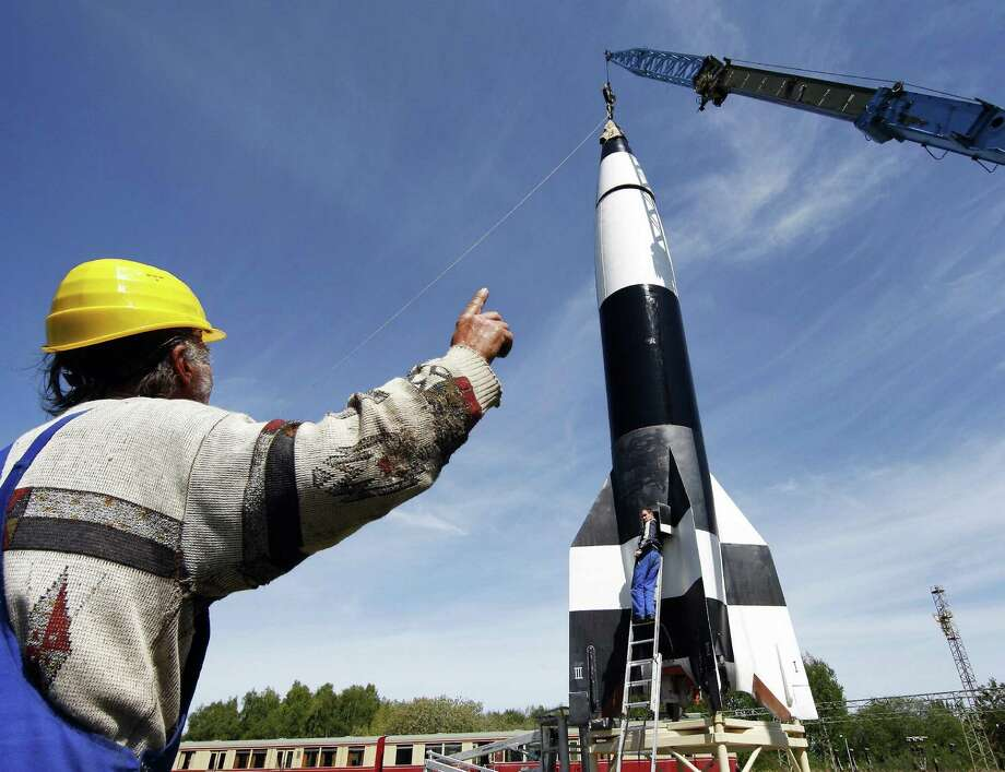 Workers use a crane to erect a reconstruction of World War II V-2 rocket