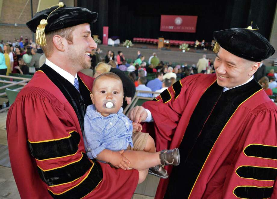 Albany Law School graduates Marshall Milligan, left, of Salt Lake City holds his 10-month-old son Myles with Alexander Li of Brooklyn at  commencement ceremonies at the Saratoga Performing Arts Center, Saratoga Springs, NY Friday May 17, 2013.  (John Carl D'Annibale / Times Union) Photo: John Carl D'Annibale / 10022118A