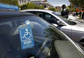 A disabled parking placard is displayed near Civic Center Plaza  on Friday May, 17, 2013 in San Francisco, Calif. People with disabilities are having trouble finding parking in San Francisco making it more difficult to access their destinations. Current disabled parking placards and blue zone policies are failing to increase access for people with disabilities and reduce parking availability for all drivers. The City's Accessible Parking Policy Advisory Committee has worked together to present a better plan.