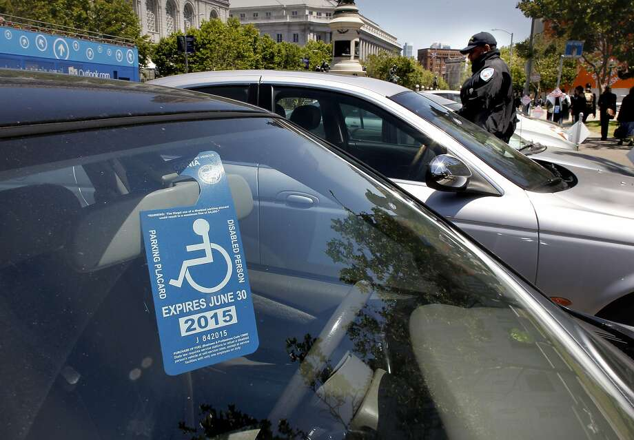 A disabled parking placard is displayed near Civic Center Plaza  on Friday May, 17, 2013 in San Francisco, Calif. People with disabilities are having trouble finding parking in San Francisco making it more difficult to access their destinations. Current disabled parking placards and blue zone policies are failing to increase access for people with disabilities and reduce parking availability for all drivers. The City's Accessible Parking Policy Advisory Committee has worked together to present a better plan. Photo: Michael Macor, The Chronicle