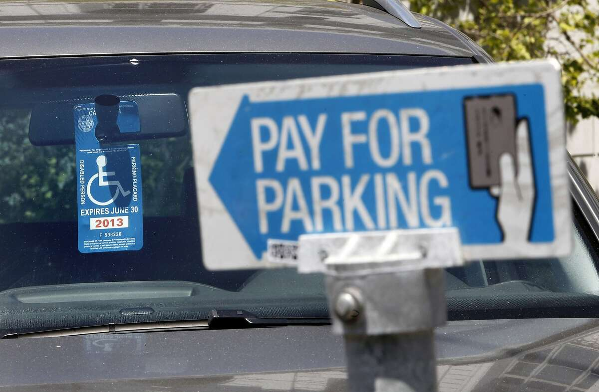 A disabled parking placard is displayed in a vehicle parked near Civic Center Plaza on Friday May, 17, 2013 in San Francisco, Calif. People with disabilities are having trouble finding parking in San Francisco making it more difficult to access their destinations. Current disabled parking placards and blue zone policies are failing to increase access for people with disabilities and reduce parking availability for all drivers. The City's Accessible Parking Policy Advisory Committee has worked together to present a better plan.