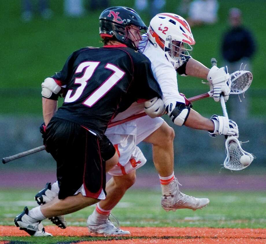 New Canaan High School's Eric Persky checks Ridgefield's Will Bonaparte in a game at Tiger Hollow Stadium earlier this year. Bonaparte and Persky are two of the premier players in the FCIAC. Photo: Scott Mullin / The News-Times Freelance