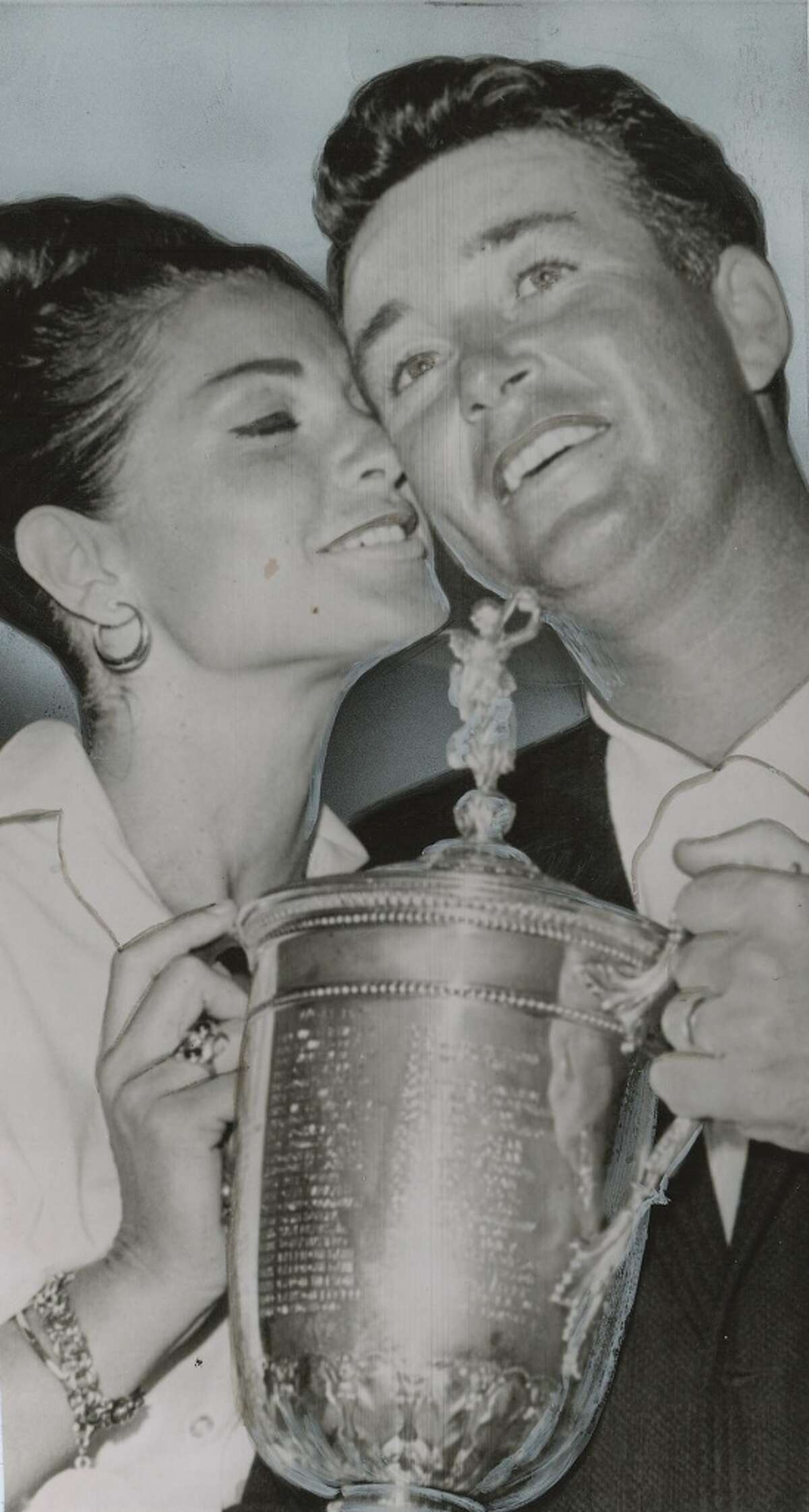 Ken Venturi, winner of the National Open gets a big kiss from his wife, Conni, as he accepts the title-holder's silver cup after a searing final round on the Washington Congressional Country Club course on June 21, 1964.
