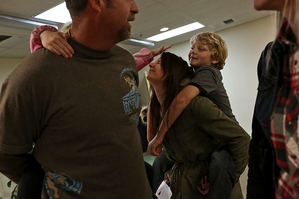 Myah Bilton-Smith, 21, plays with her half-siblings, Avrie and Asher, with her father, Mark Bilton-Smith, left, after attending her grandmother's graduation from a WINGS' seminar in Eugene, OR on March, 17, 2013.
