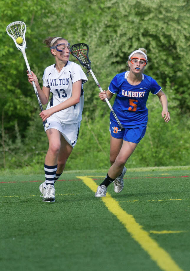Wilton's Makenna Pearsall carries the ball as she is defended by Danbury's Lindsey Eanniello during Friday's FCIAC girls lacrosse quarterfinal game at Wilton High School on May 17, 2013. Photo: Lindsay Perry / Stamford Advocate
