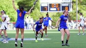 Danbury players celebrate their win after Friday's FCIAC girls lacrosse quarterfinal game at Wilton High School on May 17, 2013.