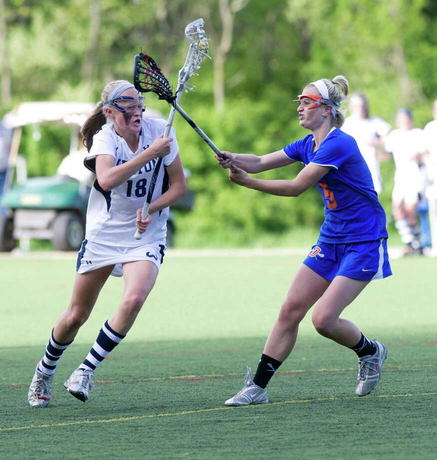 Wilton's Laura Knapp controls the ball as she is defended by Danbury's Lindsey Eanniello during Friday's FCIAC girls lacrosse quarterfinal game at Wilton High School on May 17, 2013. Photo: Lindsay Perry / Stamford Advocate