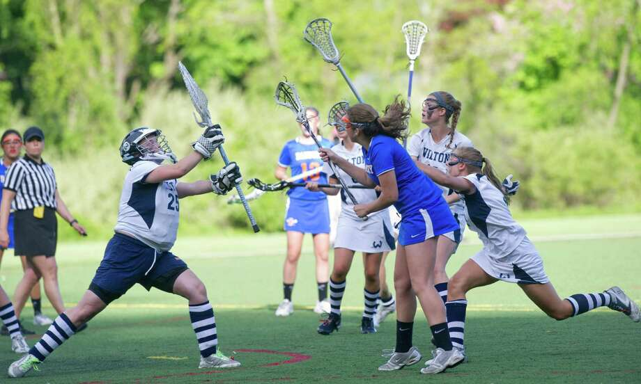Danbury's Molly Miller scores a goal in the last three seconds of overtime, giving Danbury the lead and the win during Friday's FCIAC girls lacrosse quarterfinal game at Wilton High School on May 17, 2013. Photo: Lindsay Perry / Stamford Advocate