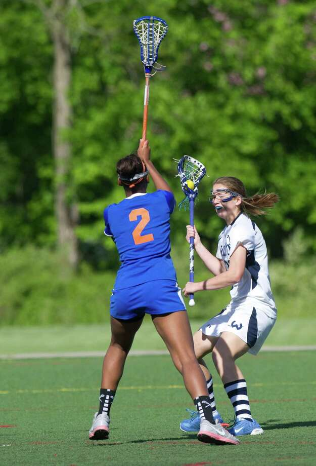 Wilton's Sara Dickinson controls the ball as she is defended by Danbury's Najmah James during Friday's FCIAC girls lacrosse quarterfinal game at Wilton High School on May 17, 2013. Photo: Lindsay Perry / Stamford Advocate