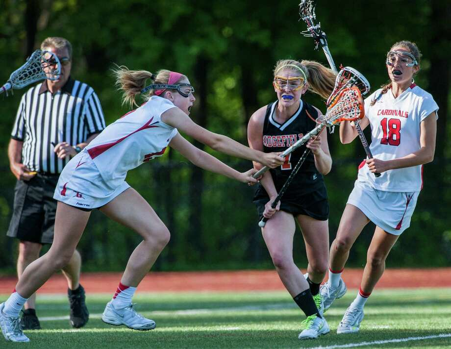 Ridgefield high school's Liana Mathias tries to get by Greenwich high school's Jenny Goggin during a FCIAC quarterfinal girls lacrosse game played at Greenwich high school, Greenwich, CT on Friday, May 17th, 2013. Photo: Mark Conrad / Stamford Advocate Freelance