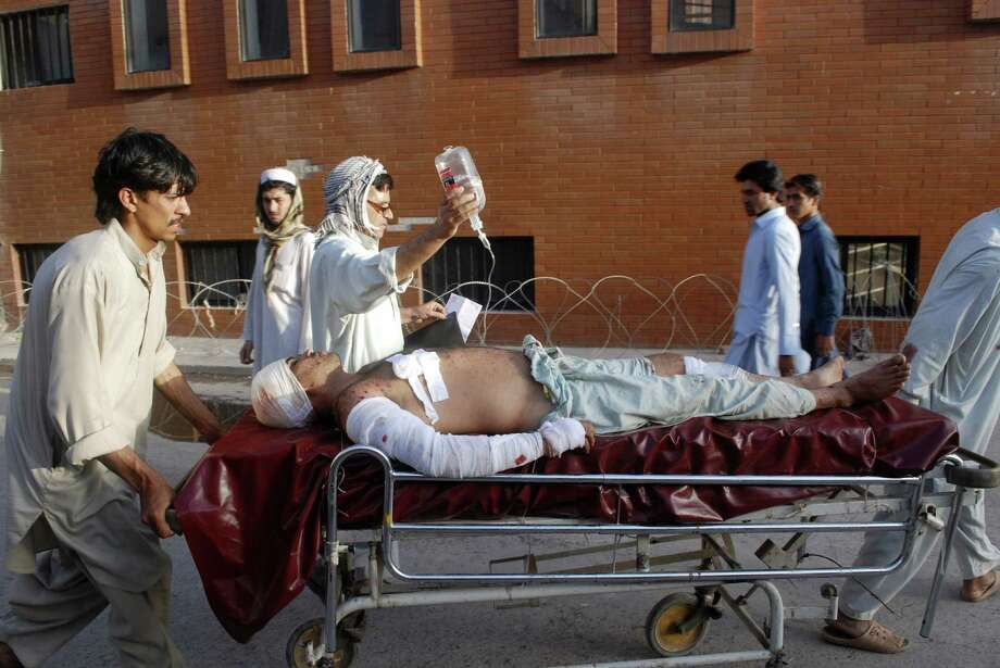 A man who was injured in a bombing at a mosque in Baz Darrah village is taken to a hospital in Peshawar, Pakistan. A second bombing occurred at a second mosque nearby.