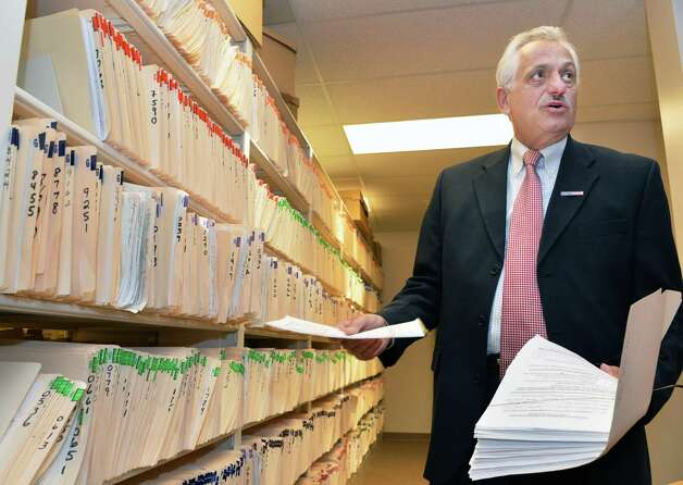 Rensselaer County Clerk Frank Merola holds a stack of signed pistol permit opt-out requests next to rows of 20,000 pistol permits in the records room of the County Clerk's office in Troy, NY Friday May 17, 2013.  (John Carl D'Annibale / Times Union) Photo: John Carl D'Annibale / 00022478A