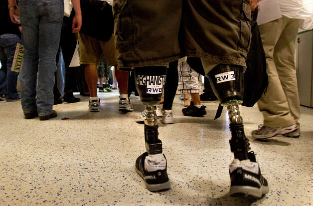 Wounded Warrior Heroes make their way through Bush Intercontinental Airport after arriving Friday, May 17, 2013, in Houston. The arrival of the wounded warriors kicked off Warrior Weekend in which wounded veterans participate in a deep-sea fishing trip in Port O'Connor. Photo: Cody Duty, Houston Chronicle / © 2013 Houston Chronicle