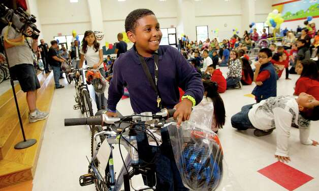 Natice Alford, 10, walks away with his bike as 95 Coop Elementary School  fifth-grade students received a bicycle, a helmet, and a bicycle lock-Coop Elementary students as part of the Bikes for Excellence program Friday, May 17, 2013, in Houston. Photo: Johnny Hanson, Houston Chronicle / © 2013  Houston Chronicle