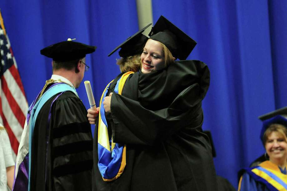 Graduate Katelyn LaPorte, right, embraces her mother, Laura, a faculty member who presented Katelyn with her diploma, during the college commencement on Friday, May 17, 2013, at Fulton-Montgomery Community College in Johnstown, N.Y. (Cindy Schultz / Times Union) Photo: Cindy Schultz / 10022126A