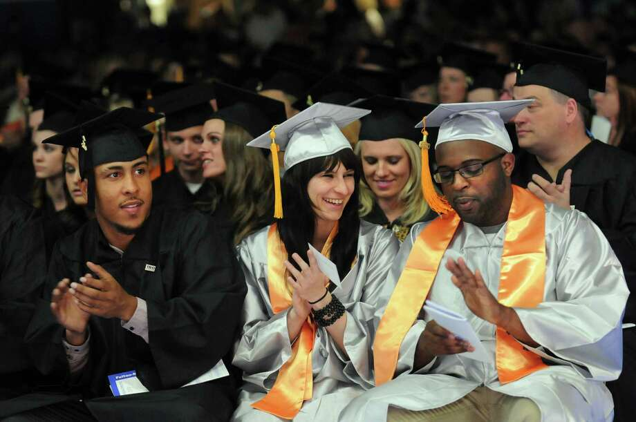 Graduates Jeffery Rodriguez, left, Santa Pumpura, center, and Darnnell Jeffers applaud the speakers during college commencement on Friday, May 17, 2013, at Fulton-Montgomery Community College in Johnstown, N.Y. (Cindy Schultz / Times Union) Photo: Cindy Schultz / 10022126A