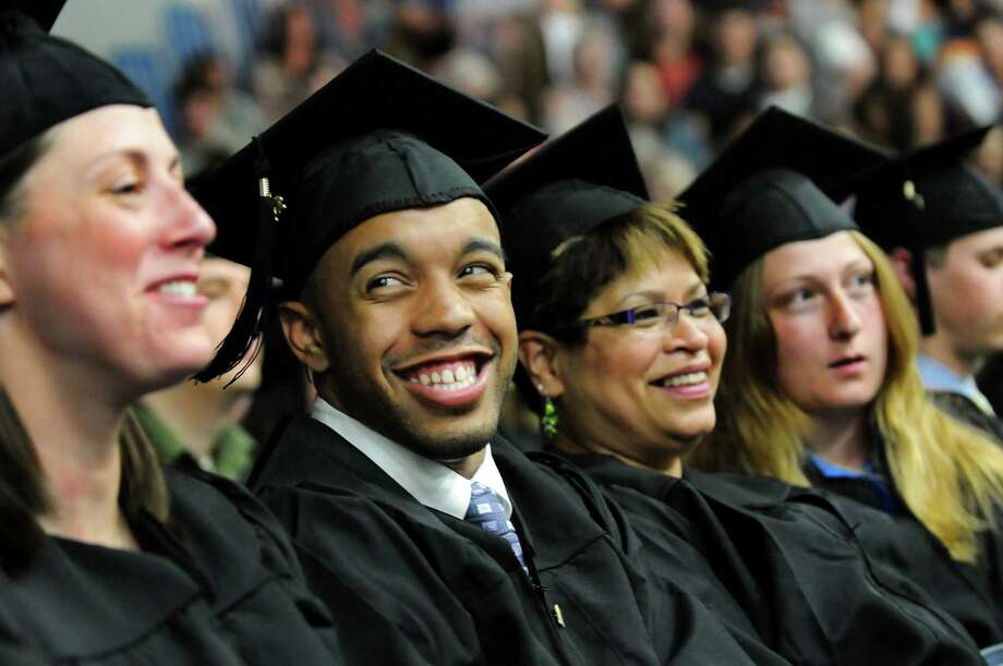 Graduate Thomas Santiago, second from left, enjoys the moment during college commencement on Friday, May 17, 2013, at Fulton-Montgomery Community College in Johnstown, N.Y. Joining him are graduates Jennifer Rymer, left, Elaine Santiago, center, and Alida Scott. (Cindy Schultz / Times Union) Photo: Cindy Schultz / 10022126A