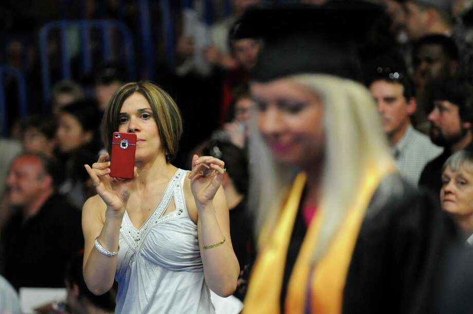 Maria Mastrocinque, left, waits to photograph her friend Elena O'Brien, right, during college commencement on Friday, May 17, 2013, at Fulton-Montgomery Community College in Johnstown, N.Y. (Cindy Schultz / Times Union) Photo: Cindy Schultz / 10022126A