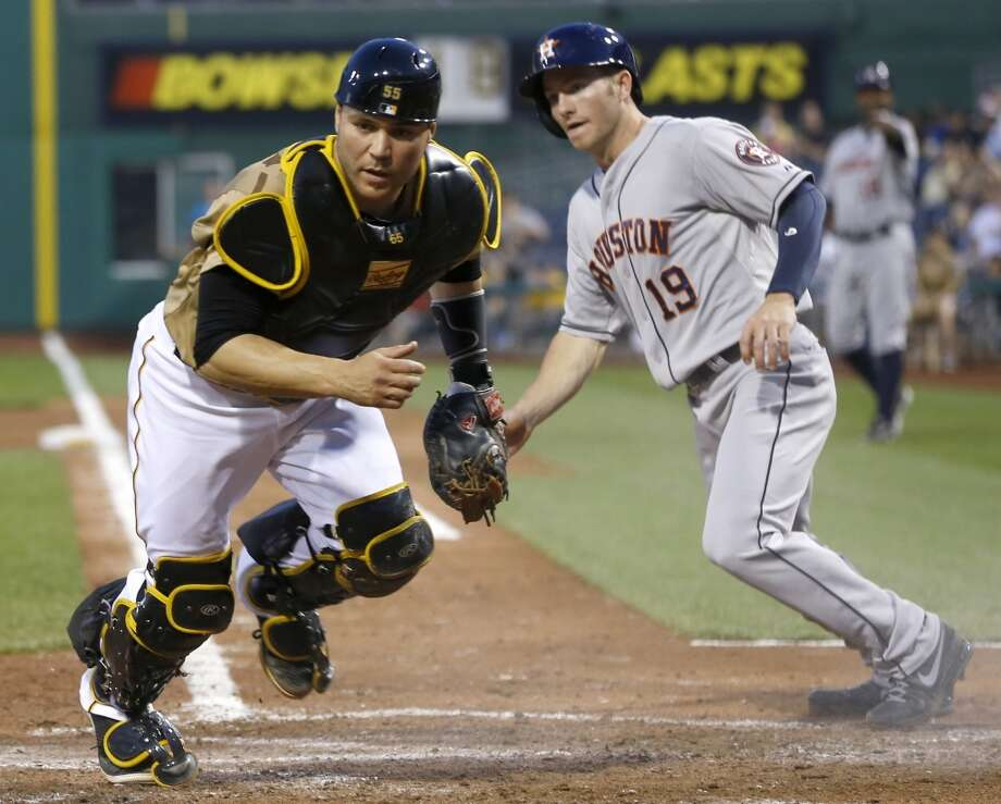 Pirates catcher Russell Martin,  looks for the ball as Robbie Grossman of the Astros scores on a double steal and a bad throw by second baseman Neil Walker in the fifth inning.