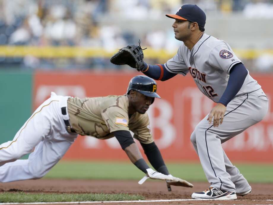 Astros first baseman Carlos Pena waits for a pickoff attempt as Starling Marte of the Pirates dives back to first base during the first inning