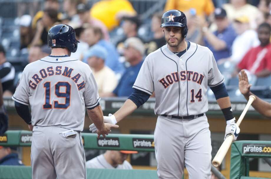 Robbie Grossman of the Astros is congratulated by teammate J.D. Martinez after scoring a run against the Pirates.