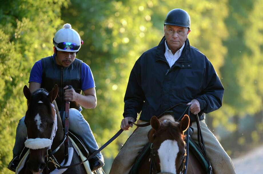 Trainer D. Wayne Lukas returns Preakness combatant Oxbow, left, back to the barn after his morning exercise May 17, 2013 the day before the second jewel of the Triple Crown for thoroughbreds to be held at the Pimlico Race Course in Baltimore, MD.  (Skip Dickstein/Times Union) Photo: SKIP DICKSTEIN