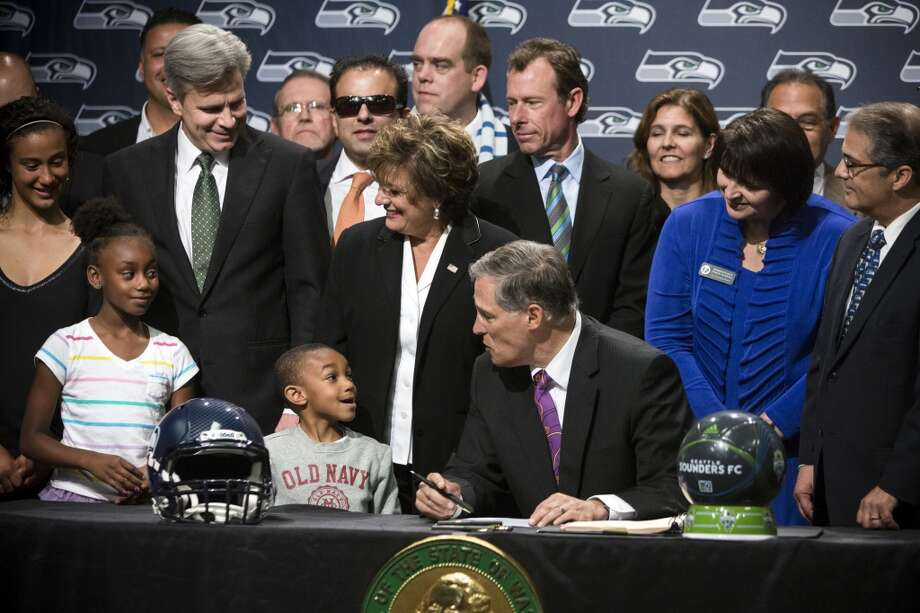 Gov. Jay Inslee, center right, chats with Kobe Thomas, 4, center left, and his sister, Sydney Thomas, 8, left, while signing a bill unveiling the new Washington state Seahawks and Sounders FC themed license plates Friday, May 17, 2013, at the Virginia Mason Athletic Center in Renton. The new plates will be available for purchase on Jan. 1, 2014.  Photo: JORDAN STEAD, SEATTLEPI.COM