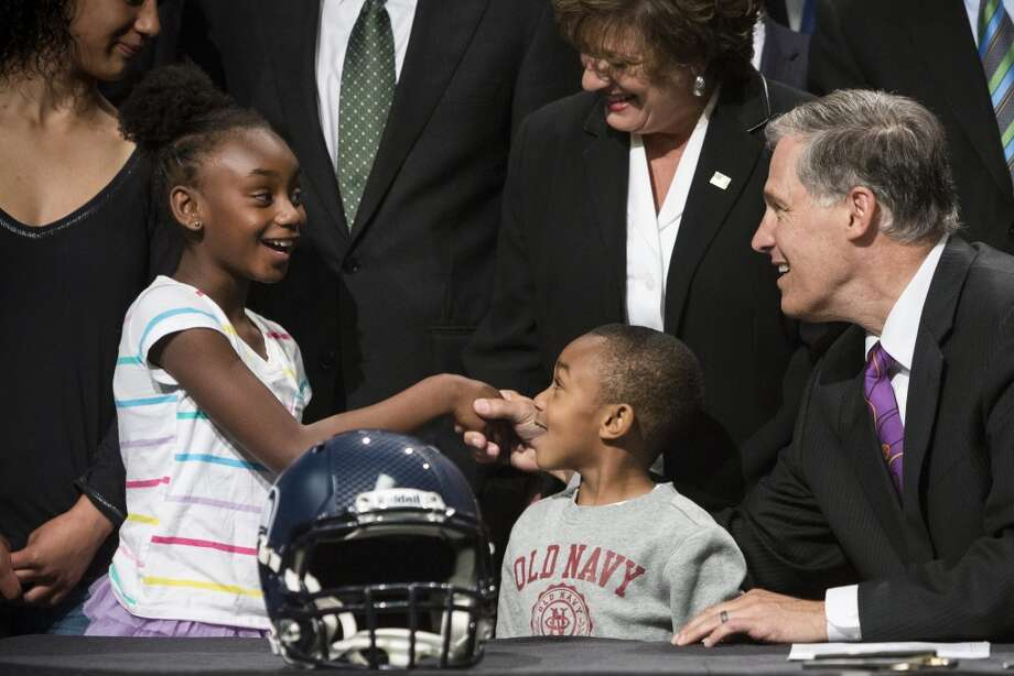 Gov. Jay Inslee, right, chats with Kobe Thomas, 4, center, and his sister, Sydney Thomas, 8, left, after signing a bill unveiling the new Washington state Seahawks and Sounders FC themed license plates Friday, May 17, 2013, at the Virginia Mason Athletic Center in Renton. The new plates will be available for purchase on Jan. 1, 2014.  Photo: JORDAN STEAD, SEATTLEPI.COM