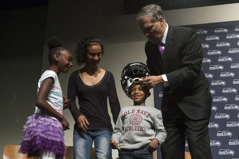 Gov. Jay Inslee, right, jokingly puts a helmet on Kobe Thomas, 4, center right, while Keanna Beaver, center left, and Sydney Thomas, 8, left, look on after the signing of a bill to unveil the new Washington state Seahawks and Sounders FC themed license plates Friday, May 17, 2013, at the Virginia Mason Athletic Center in Renton. The new plates will be available for purchase on Jan. 1, 2014.  Photo: JORDAN STEAD, SEATTLEPI.COM