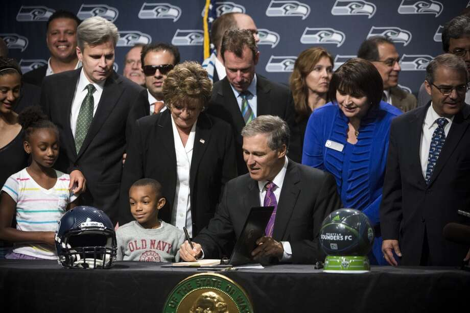 Gov. Jay Inslee, center, signs a bill at the unveiling of the new Washington state Seahawks and Sounders FC themed license plates Friday, May 17, 2013, at the Virginia Mason Athletic Center in Renton. The new plates will be available for purchase on Jan. 1, 2014.  Photo: JORDAN STEAD, SEATTLEPI.COM