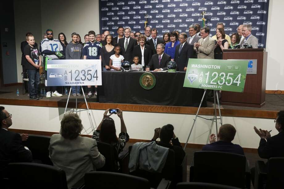 Gov. Jay Inslee, center, prepares to sign a bill and unveil the new Washington state Seahawks and Sounders FC themed license plates Friday, May 17, 2013, at the Virginia Mason Athletic Center in Renton. The new plates will be available for purchase on Jan. 1, 2014.  Photo: JORDAN STEAD, SEATTLEPI.COM
