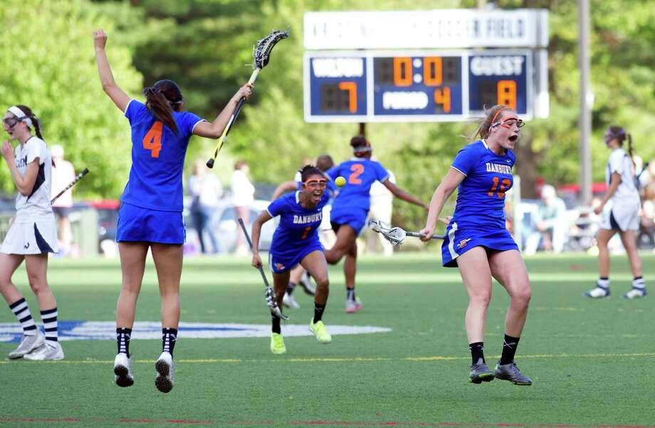 Danbury players celebrate their win after Friday's FCIAC girls lacrosse quarterfinal game at Wilton High School on May 17, 2013. Photo: Lindsay Perry / Stamford Advocate