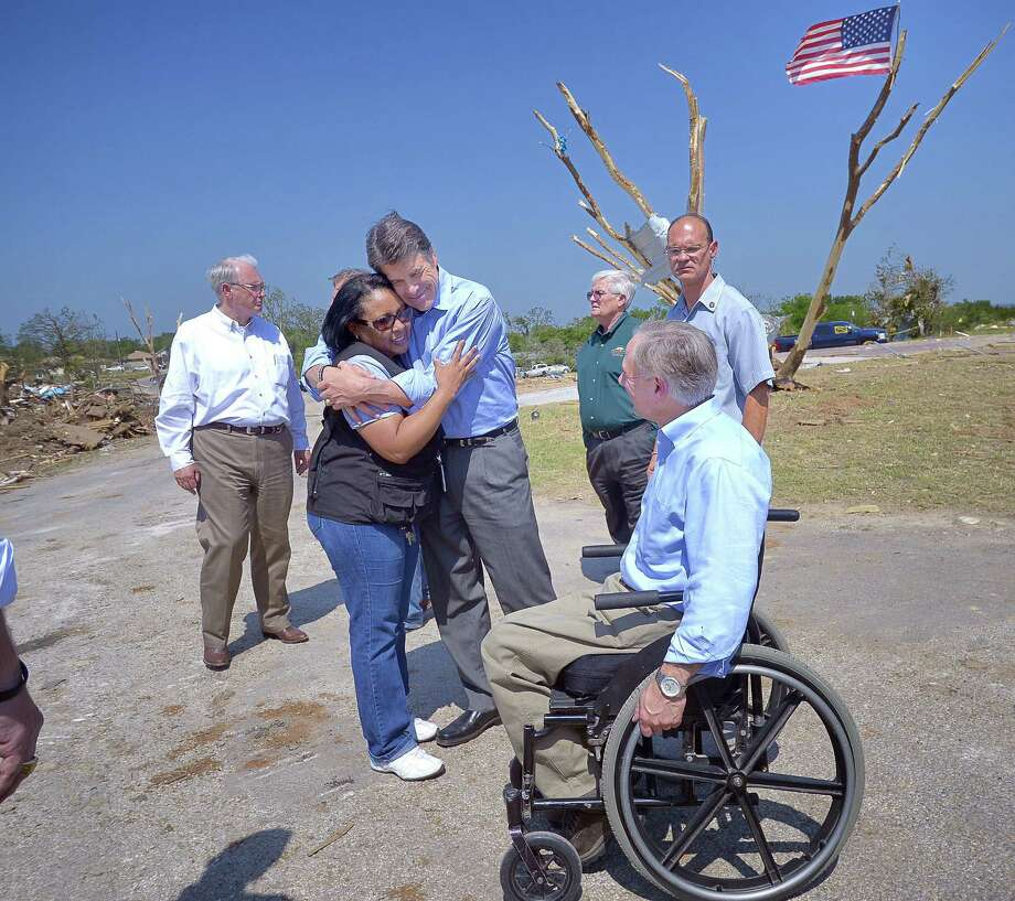 Gov. Rick Perry hugs Tonya Solis-Mosby of the American Red Cross as Attorney General Greg Abbott, looks on in the Rancho Brazos Estates subdivision near Granbury. Photo: Max Faulkner / Fort Worth Star-Telegram