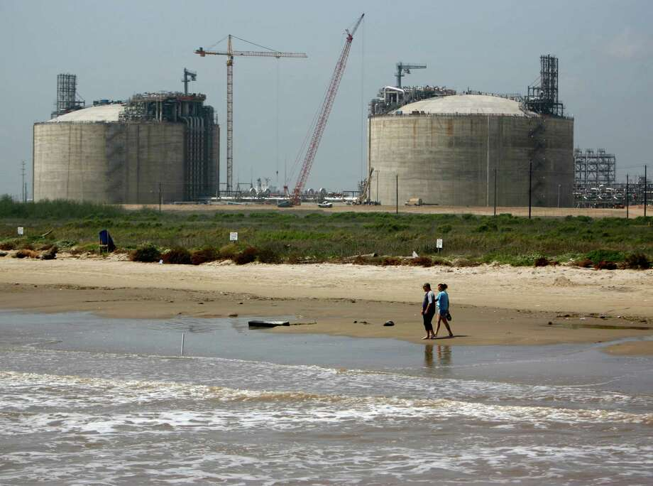 Jacob Savinski, left, and Belinda Collins, right  walk on the Quintana Beach, near the Freeport LNG terminal ( in the background) Thursday, March 27, 2008.  The Freeport LNG will start taking shipments next month and says it's the first onshore LNG terminal to come online for 25 years.   ( Karen Warren / Chronicle ) Photo: Karen Warren, Staff / Houston Chronicle