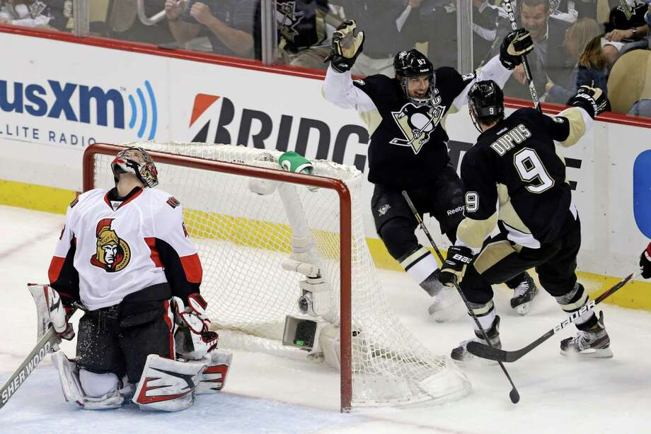Pittsburgh Penguins' Sidney Crosby (87) celebrates with teammate Pascal Dupuis (9) as Ottawa Senators goalie Craig Anderson (41) reacts to Crosby's second goal of the first period of Game 2 of an NHL hockey Stanley Cup second-round playoff series, in Pittsburgh on Friday, May 17, 2013. (AP Photo/Gene J. Puskar) Photo: Gene J. Puskar