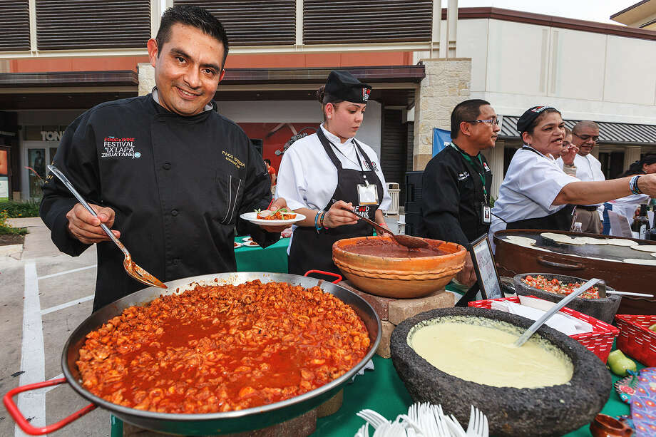 """Chef Paco Isordia (left) from the Viceroy Zihuantanejo Hotels and Resort prepares seafood a la talla during the Best of Mexico event on Main Street at the Shops at La Cantera. """"I enjoy visiting this city,"""" he said in Spanish. """"The people are very nice here."""" Photo: Marvin Pfeiffer / San Antonio Express-News"""