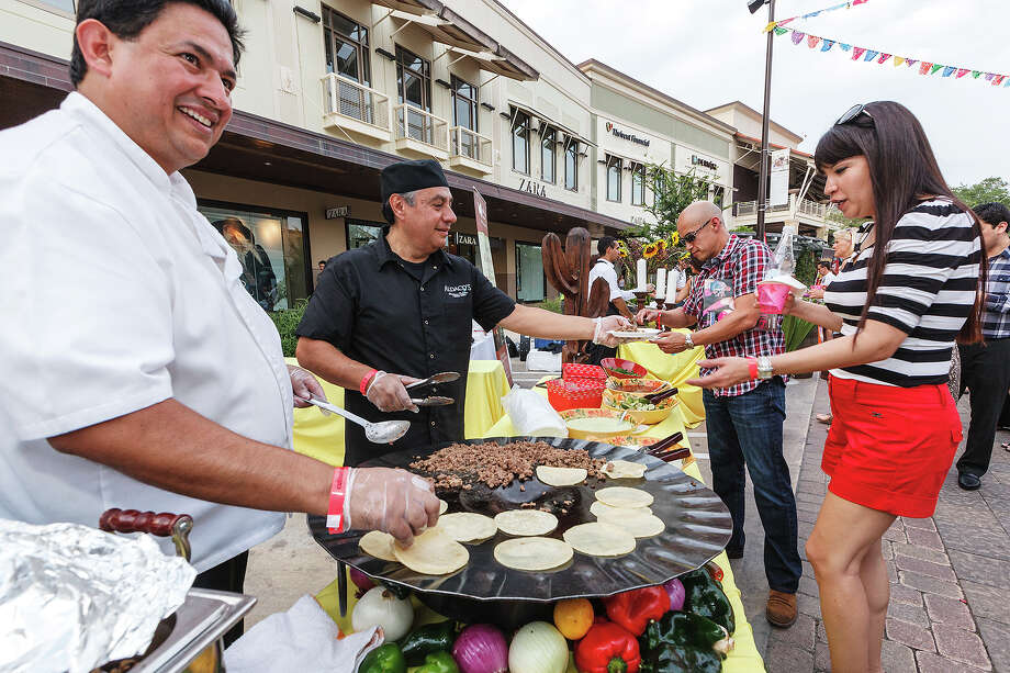 Henry Talamantez (from left) and Francisco Pineda with Aldaco's Mexican Cuisine, serve tacos to Michael and Laura Gonzales at the Best of Mexico event on Main Street at The Shops at La Cantera on Friday, May 17, 2013.  The event was presented with the Culinaria wine and food festival and showcased interior Mexican cuisine and higher-end drinks.  MARVIN PFEIFFER/ mpfeiffer@express-news.net Photo: Marvin Pfeiffer/ Express-News / Express-News 2013