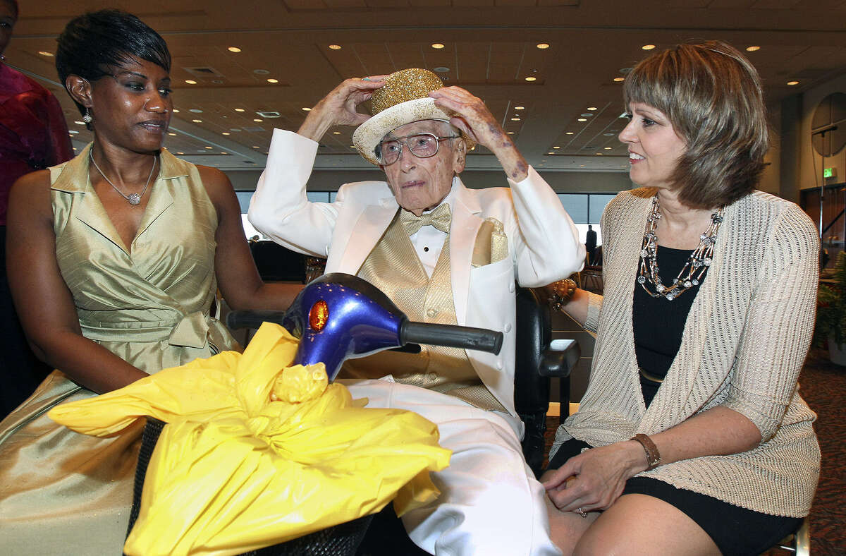 Bill Sinkin puts on his party hat as he waits for birthday festivities to begin with his personal assistants Rosie Hardeman (left) and Tina Grau in the Rosenberg Skyroom at the University of the Incarnate Word on May 17, 2013.