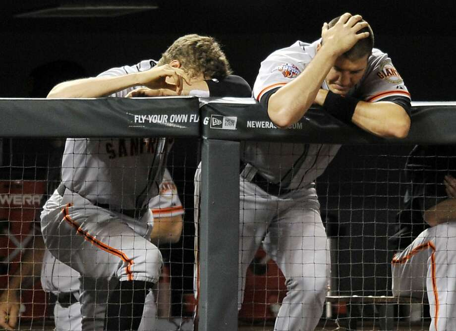 The Giants' Hunter Pence (left) and Brett Pill can't bear to watch during the ninth inning in Colorado. Photo: Jack Dempsey, Associated Press