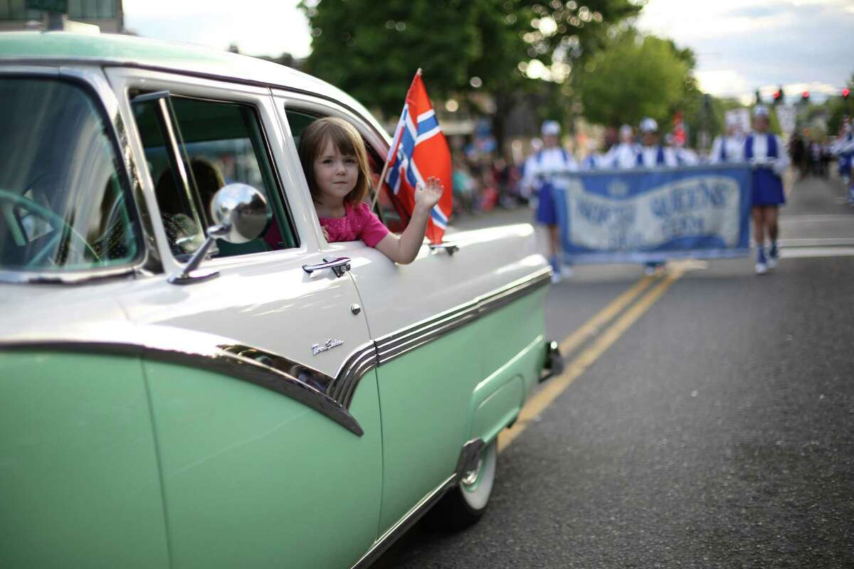 A parade participant waves from a classic car during Ballard's annual Syttende Mai parade. The parade celebrates Norwegian Constitution Day and is one of the largest celebrations outside of Oslo. Photographed on Friday, May 17, 2013.