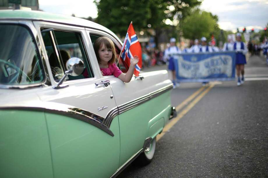 A parade participant waves from a classic car during Ballard's annual Syttende Mai parade. The parade celebrates Norwegian Constitution Day and is one of the largest celebrations outside of Oslo. Photographed on Friday, May 17, 2013. Photo: JOSHUA TRUJILLO / SEATTLEPI.COM