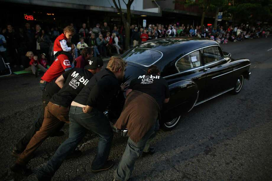 People push a car that broke down during Ballard's annual Syttende Mai parade. The parade celebrates Norwegian Constitution Day and is one of the largest celebrations outside of Oslo. Photographed on Friday, May 17, 2013. Photo: JOSHUA TRUJILLO / SEATTLEPI.COM