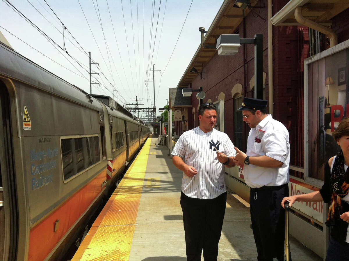 Pete Pellegrino of Worcester, Mass. speaks with a Metro-North conductor at the South Norwalk train station. Metro-North service has been indefinitely suspended between South Norwalk and New Haven forcing many Outer New Haven Line passnegers to make alternate transortation plans.